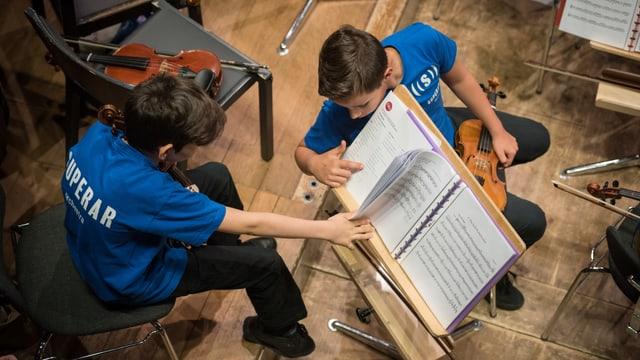 Zwei junge Violinisten in blauen T-Shirts mit der Aufschrift Superar schauen in Noten auf einem Ständer