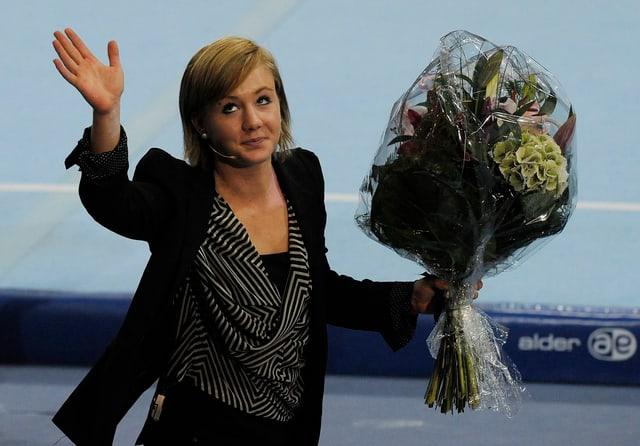 Frau mit einem riesigen Blumenstrauss winkt wehmütig in die Runde.