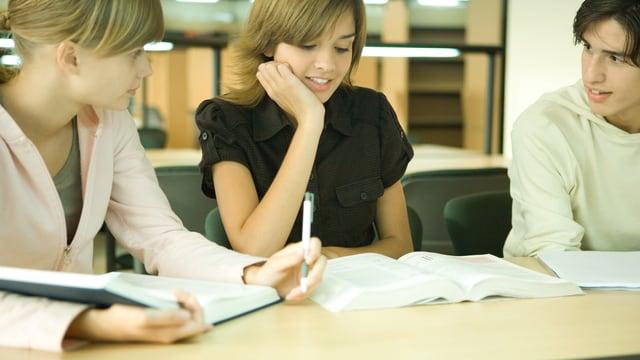 Zwei Mädchen und ein Junge sitzen vor ihren Büchern und diskutieren.