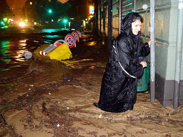 Eine Frau watet durch braunes Wasser.