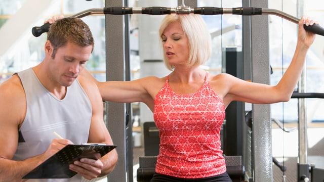 Ein Fitnesstrainer macht Notizen, während seine Kundin an einem Gerät trainiert.