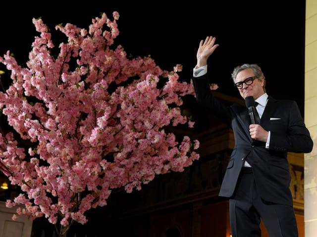 Colin Firth steht vor einem Baum mit rosaroten Blüten und hält ein Mikrofon in der linken Hand.