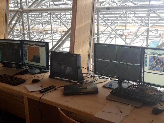 Im Vordergrund stehen viele Bildschirme auf einem Holztisch, Blick zum Fenster hinaus zeigt die Rückseite der Tribüne.