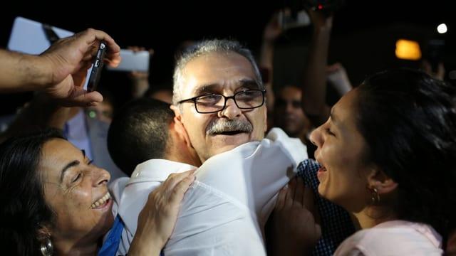 Angehörige umarmen den lachenden Journalisten Onder Celik, nachdem er freigelassen wurde.