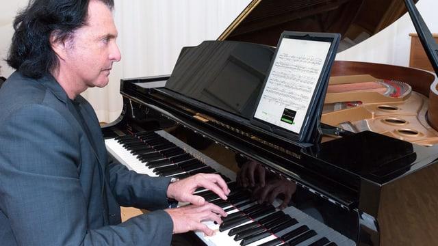 Ein Pianist spielt Klavier und schaut auf ein digitales Notenpult.