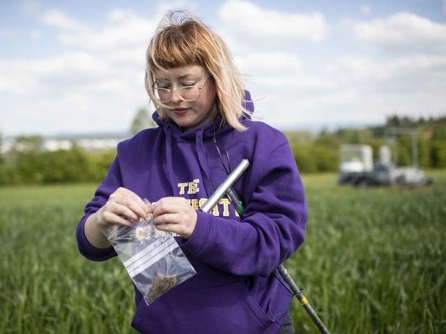 Eine Frau auf einem Feld mit einem Mess-Instrument.
