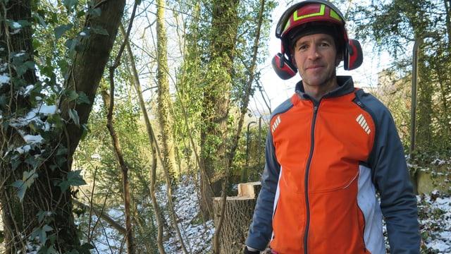 Mann mit Schutzhelm und oranger West im Wald.