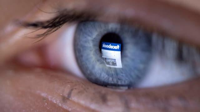 In einem Auge spiegelt sich das Logo von Facebook.