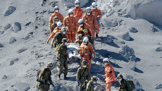 Retter tragen eine Bahre vom Vulkan hinunter