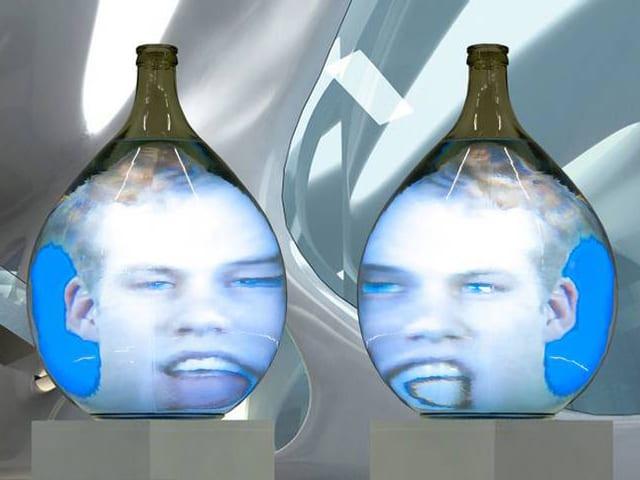 Zwei Videoprojektionen mit Gesichtern auf Glasobjekte projiziert.