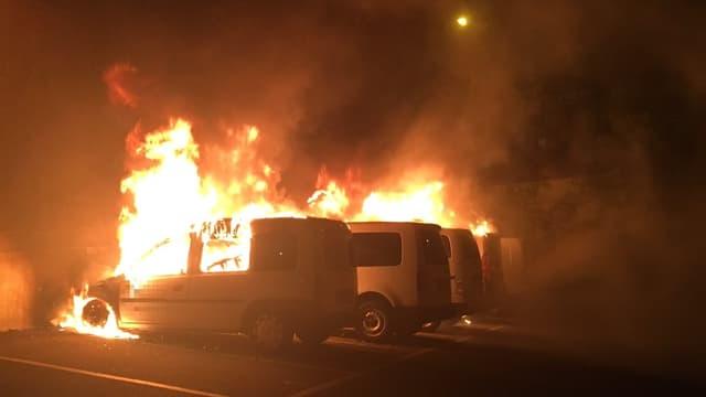 mehrere kleine, weisse Lieferwagen brennen