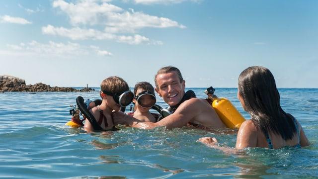 Ein junger Cousteau, seine Frau und ihre zwei Kinder schwimmen im Mittelmeer. Auf dem Rücken haben sie Sauerstoffflaschen.