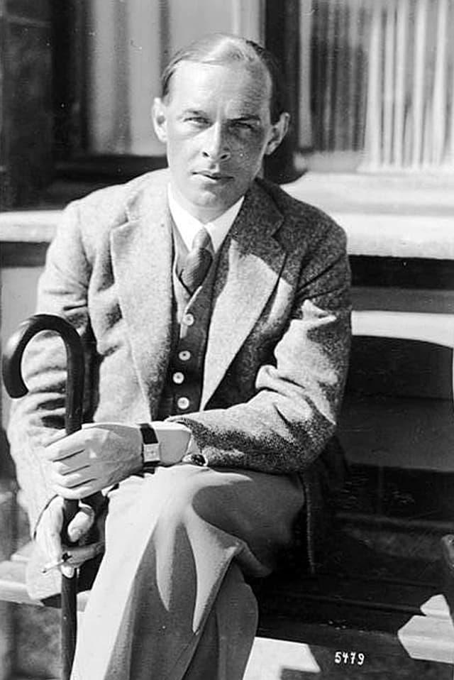 Erich Maria Remarque sitzt auf einer Bank in der Sonne, elegant gekleidet in Anzug und mit Schirm.