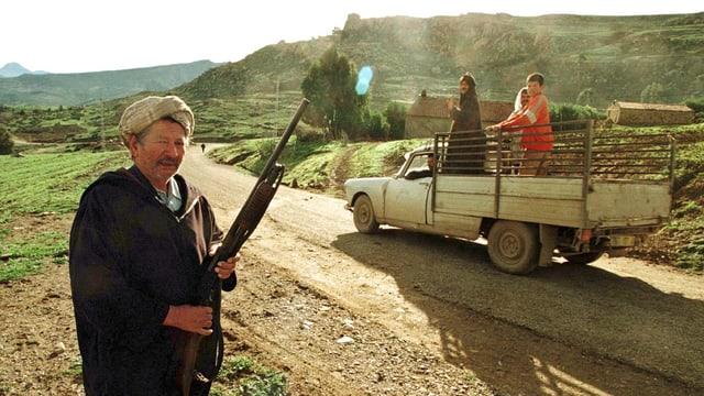 Ein Mann mit einem Gewehr im Vordergrund, dahinter fährt auf einer unbefestigten Strasse ein Pick-Up vorbei.