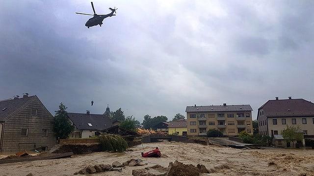 Über die Ufer getretener Fluss in Simbach. Helikopter am Himmel.