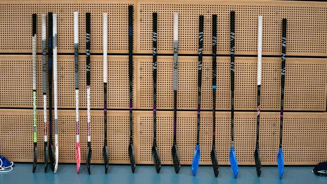 14 Hockeystöcke an einer Wand.