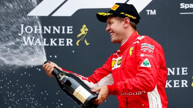 Sebastian Vettel cun ina buttiglia da Champagner.