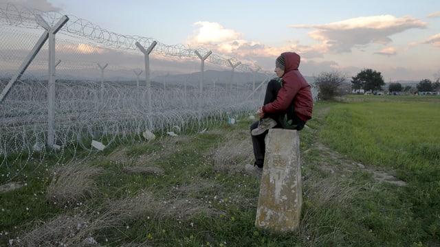 Mann sitzt auf einem Stein und schaut über durch einen Grenzzaun.