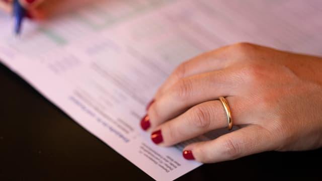 Frauenhände füllen Steuererklärung aus.