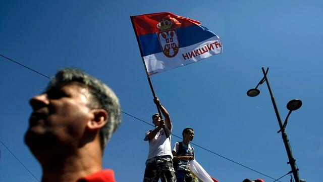 Männer, die eine serbische Fahne in der Hand halten.