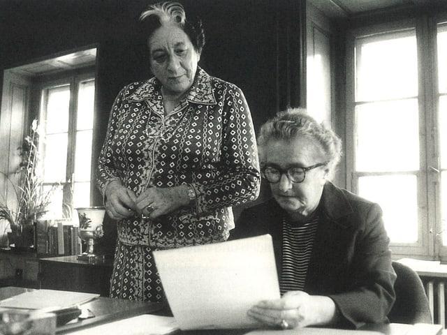 Marguerite Steiger und Hermine Raths arbeiten mit Akten an einem Schreibtisch.