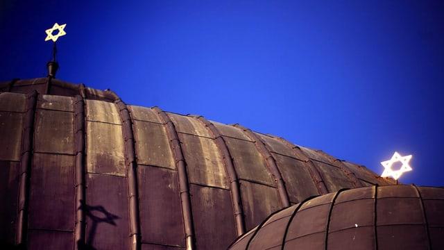 Das Dach einer Synagoge, darauf zwei in der Nacht leuchtende Davidsterne.