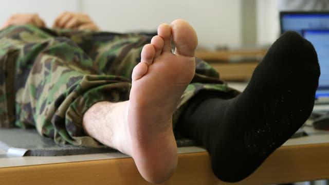 Ein Rekrut liegt auf einer Pritsche. Von einem Fuss wurde die Socke entfernt. Blasen sind zu sehen.