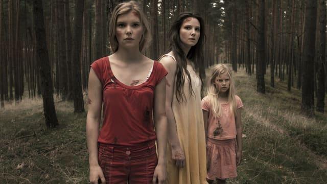 Drei Frauen stehen im Wald.