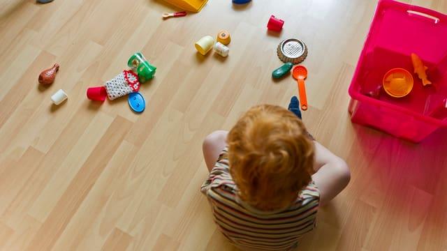 Kind sitzt am Boden mit Spielsachen.