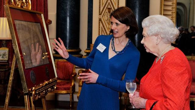 Zwei Frauen betrachten ein Stück beschriebenes Papier, das hinter Glas auf einer Staffelei aufgestellt ist.