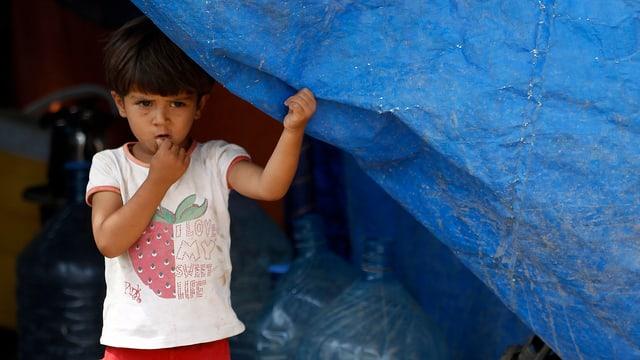 Ein Kind schaut hinter einer blauen Zeltplane hervor.