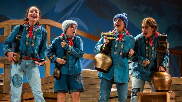 Vier Mädchen mit Kuhglocken und Folklorehemden.