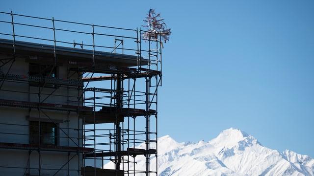Hausfassade mit Baugerüst vor verschneiten Bergen.