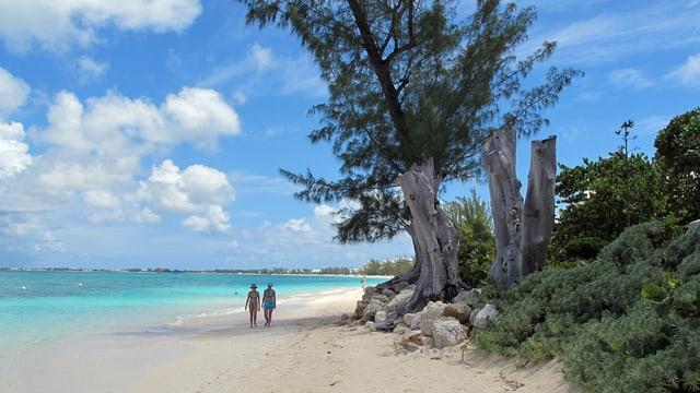 Zwei Frauen spazieren am Strand der Cayman Islands.