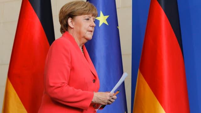 Angela Merkel vor Fahnen der BRD und der EU