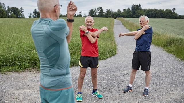 Drei ältere Luzerner Männer in Jogging-Anzügen stretchen ihre Arme.