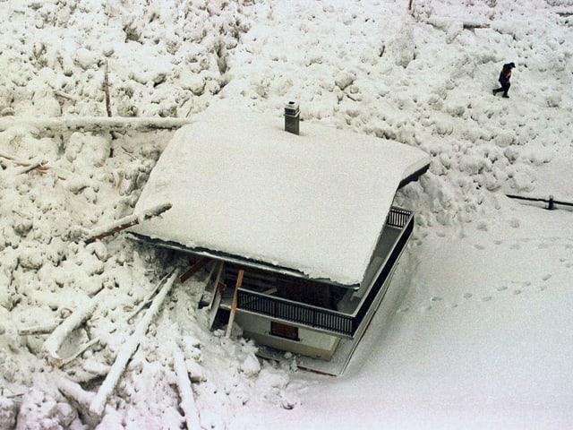 Bäume und Schneemassen liegen auf und neben einem Chalet