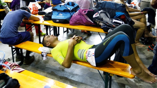 2 Männer erholen sich vom Marathon, sie liegen erschöpft auf einer Sitzbank