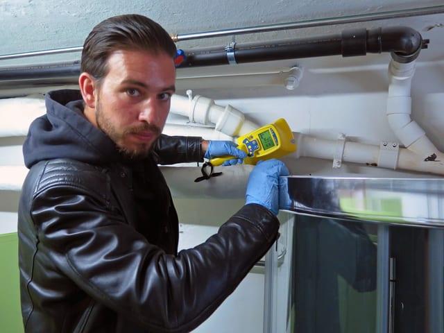 Ein Mann in schwarzer Lederjacke und blauen Plastikhandschuhen misst mit einem gelben Gerät in einem Raum mit Rohren.