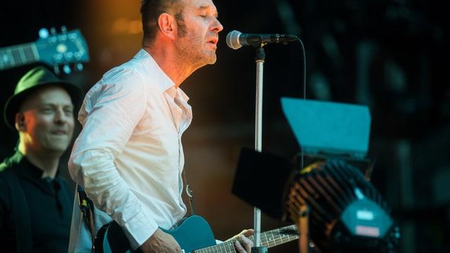 Ein Mann mit Gitarre steht am Mikrofon und singt.