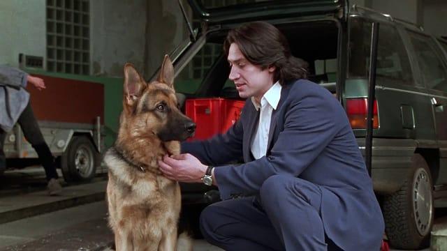 Ein Schäferhund und daneben ein Mann mit dunklem Haar und Anzug.