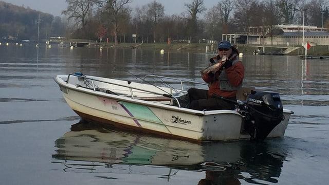 Fischer in Boot hält Fisch in die Höhe