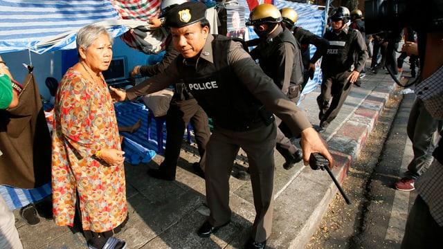 Ein thaliändischer Polizist bittet eine alte Frau zum Verlassen eines Protestcamps