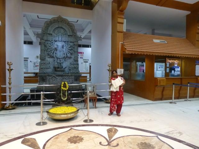 Eine Frau steht vor dem Eingang von Devi Shettys Herzklinik.