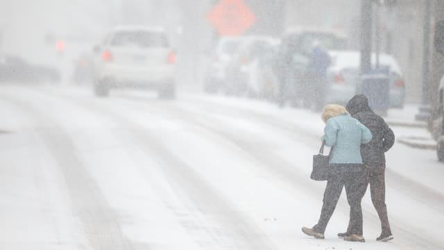 Zwei Menschen überqueren eine verschneite Strasse.