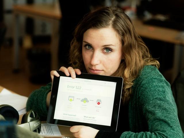 Zu sehen ist SRF 3 Mitarbeiterin Florence Fischer. Sie guckt unzufrieden. Sie zeigt einen Tabloid-Computer. Darauf ist ein Wort zu lesen: Error.