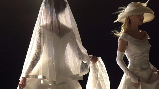 Frauen führen Brautkleider vor.
