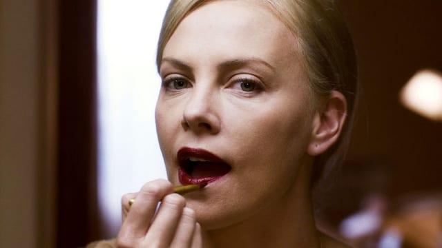 Eine Frau steht vor dem Spiegel und bemalt sich ihre Lippen rot.