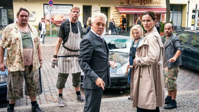 Filmbild: Sechs Menschne stehen auf einer Strasse vor einem zertrümmerten Auto. Im Vordergrund ein älterer Mann mit Anzug und eine Frau im Mantel. Dahinter drei Männer und eine Frau in schmutziger, schlecht sitzender Kleidung.
