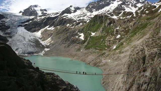 Gletscher und -see, umrahmt von Bergen, eine Hängebrücke führt über den See.